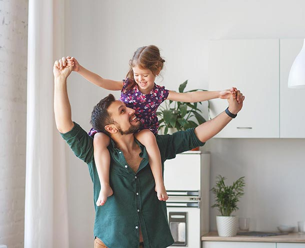 dad carrying daughter on shoulders at home